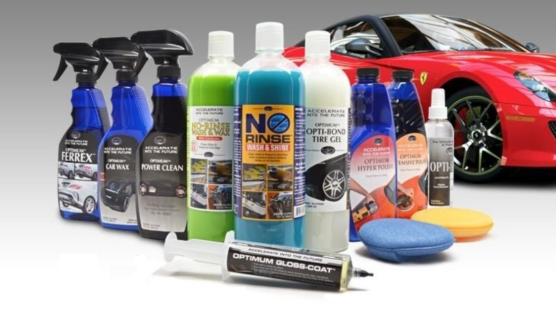 A collection of car detailing products  by a Ferrari sports car.