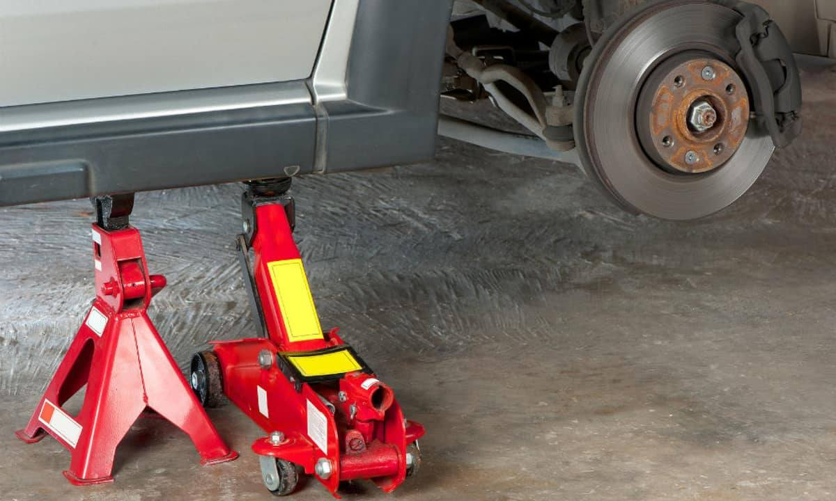 Floor jack and jack stand supporting a car