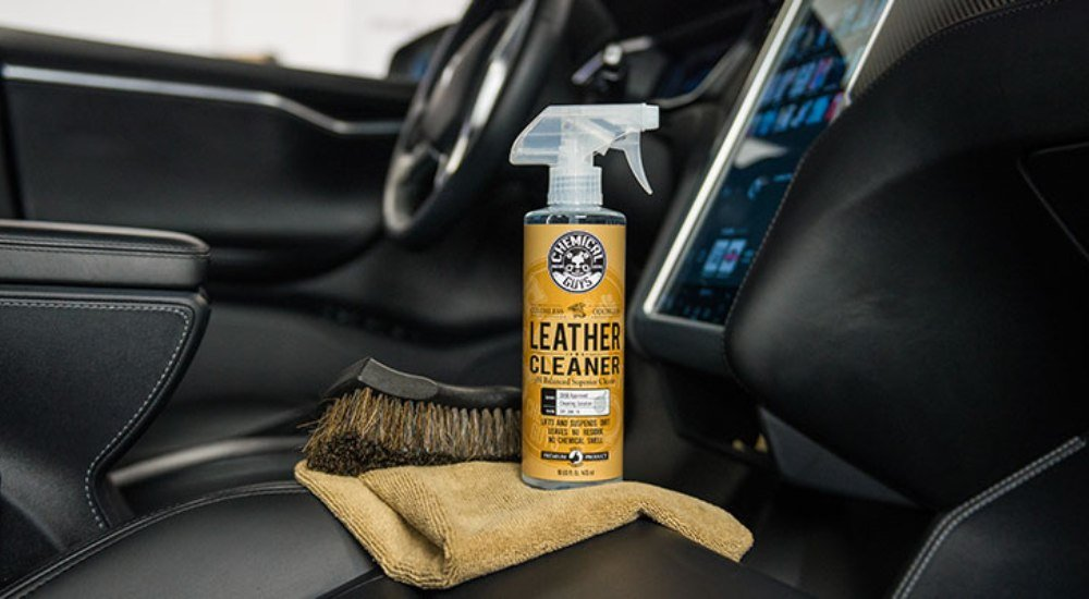 A brush, towel and spray bottle of the best leather conditioner placed on car seat