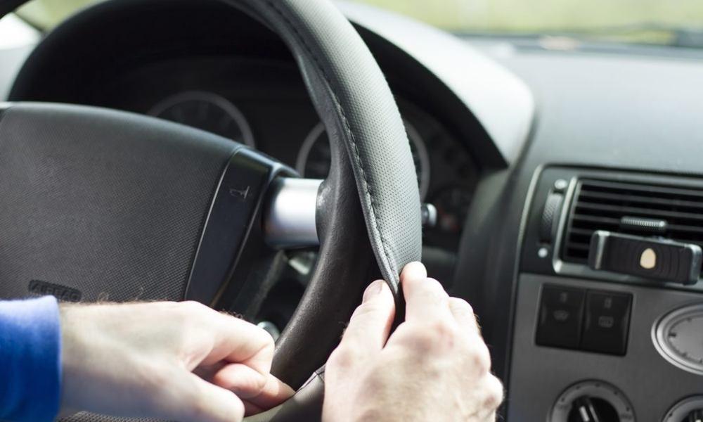 Man installing the best steering wheel cover